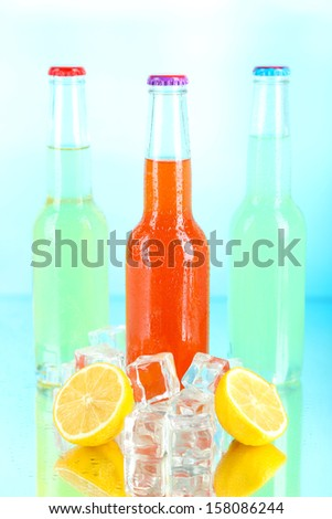 Drinks in glass bottles with ice cubes on blue background