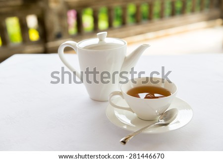 drinks, relaxation and tea party concept - tea-set of cup, pot, spoon and saucer at teahouse - stock photo