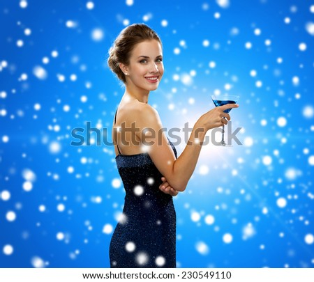 drinks, winter holidays, christmas, luxury and celebration concept - smiling woman in evening dress holding cocktail over blue snowy background - stock photo
