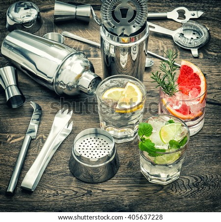 Drinks with ice and tonic water. Cocktail making accessories. Vintage style toned picture - stock photo
