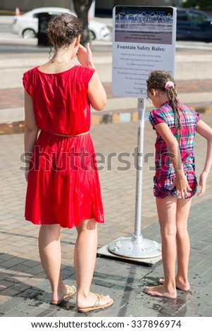 Dripping wet young woman and little girl are standing near sign. - stock photo
