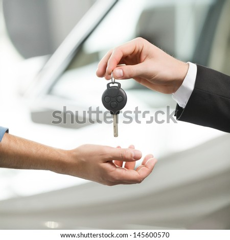 Drive carefully! Close-up shoot of the car salesman hand giving a key to the owner - stock photo