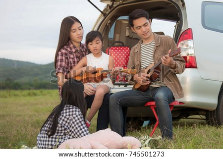 drive in the vacations family; Asian family are happy sitting in the open trunk of a car;  travel nature trip.