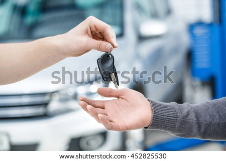 Drive safe. Cropped closeup of a car owner receiving the keys from a mechanic after repair works at the garage - stock photo