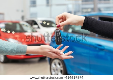 Drive safe. Cropped closeup of a female car owner receiving car keys from the car dealer manager - stock photo