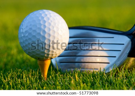 Driver behind gold ball on golf course