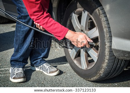 Driver checking air pressure and filling air in a tire of a car