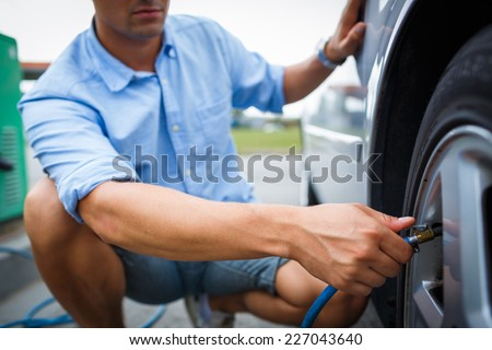 Driver checking air pressure and filling air in the tires of his modern car - stock photo
