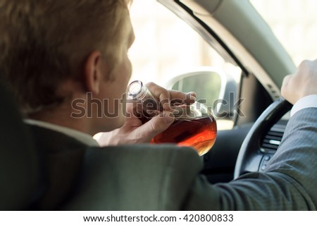 Driver drinks alcohol while sitting behind the wheel of of the car
