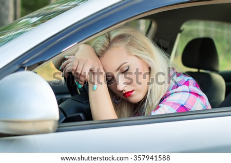 Driver girl was tired and fell asleep at the wheel of a car