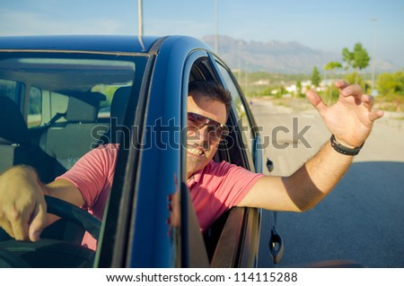 Driver hanging out of his car window gesticulating - stock photo