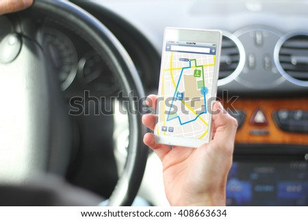 driver holding smartphone with gps app interface. All screen graphics are made up. - stock photo