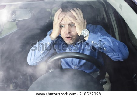Driver in horror after car accident holding his head with hands - stock photo