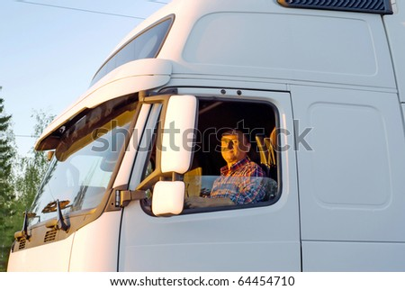 Driver in the cabin of his white truck in the evening - stock photo