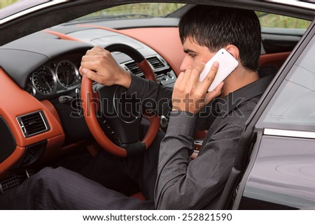Driver inside the luxury sports car talking on the phone - stock photo
