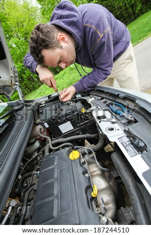 Driver is trying to repair car battery on the road - stock photo