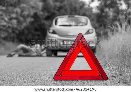 Driver lying under the broken car and warning triangle - black and white concept