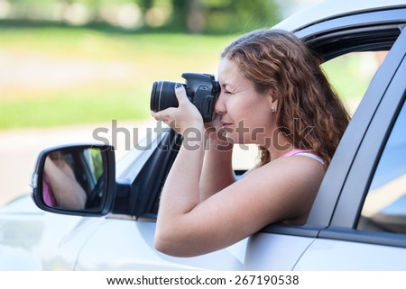 Driver photographer shooting with slr camera while sitting inside the vehicle - stock photo