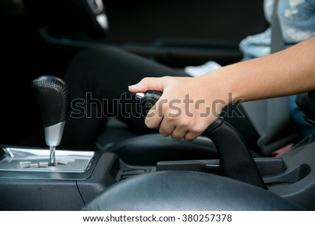 driver pulling the hand brake in car