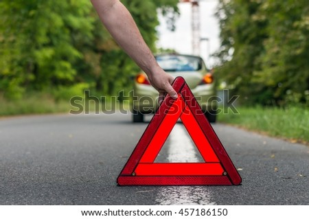 Driver putting out a traffic warning sign - broken car on the road