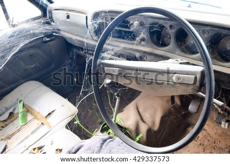 Driver's cockpit of a old car with spider web