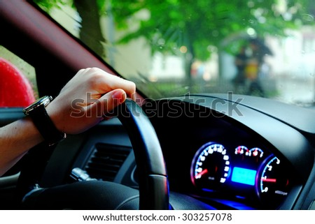 Driver's hand on a steering wheel of a car, street with green trees and incidental people on a background, close-up - stock photo