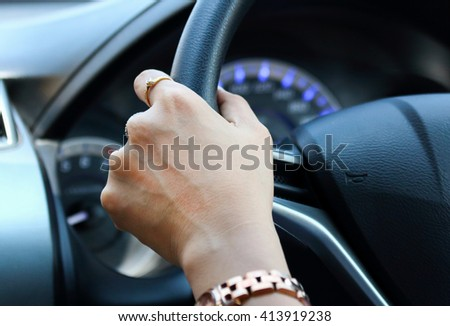 Driver's hand on the steering wheel inside of a car.