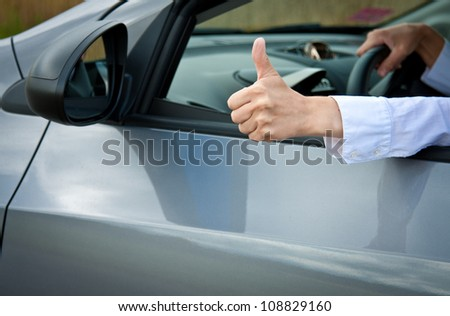 Driver's hand showing thumbs up gesture - closeup shot - stock photo