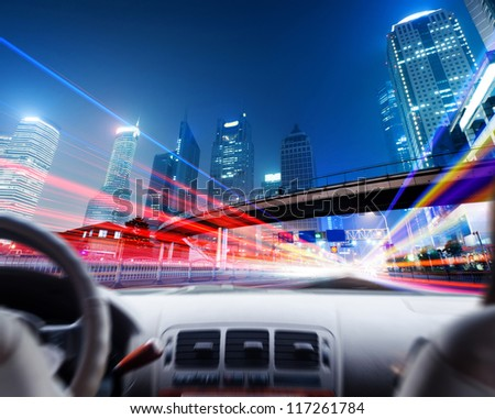 Driver's hands on a steering wheel of a car and night scene - stock photo