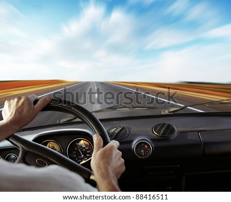 Driver's hands on a steering wheel with motion blurred road and sky