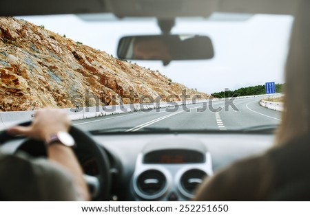 driver's hands on steering wheel inside of a car,travel in car,selective focus on the highway - stock photo