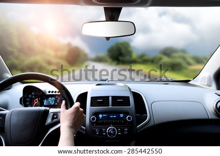 Driver's hands on the steering wheel inside of a car - stock photo