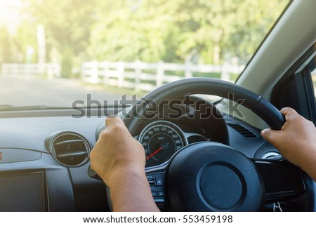 Driver's hands on the steering wheel inside of a car