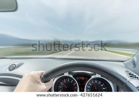 Driver's perspective in a car dashboard driving on to a scenic road. Motion blurred the view as if the driver is driving the car very fast. Cars drive very speedy fast on the road. Speeding car. - stock photo