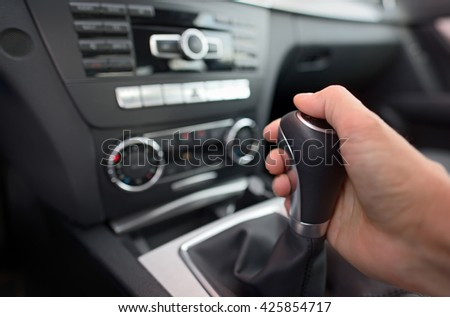 Driver shifting the gear stick in car
