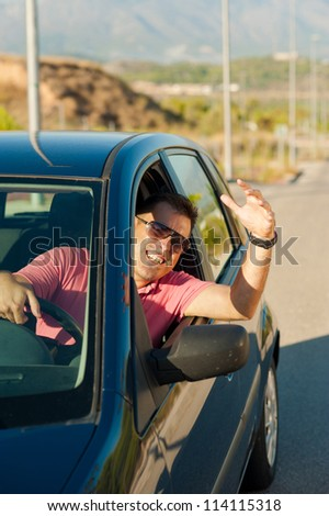Driver wildly gesticulating out of the window of his car - stock photo