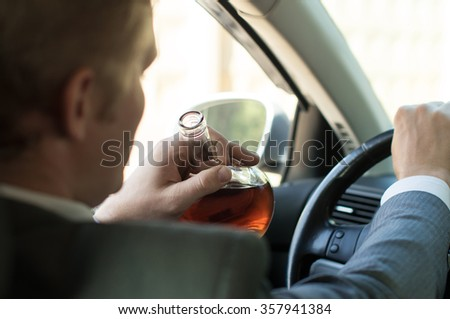 Driver with a bottle of alcohol at the wheel - stock photo