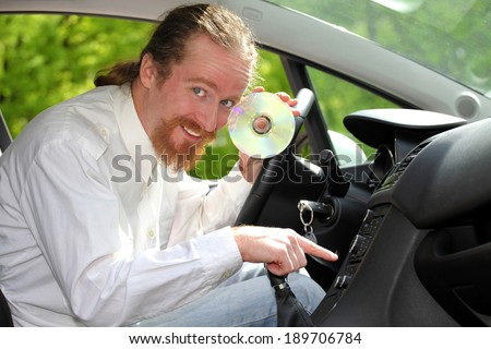 driver with CD, playing music in the car - stock photo