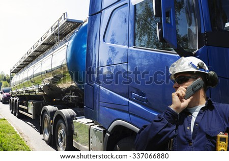 driver, worker in front of large fuel-truck, tanker truck - stock photo