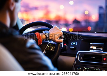 Driving a car at night -man driving his modern car at night in a city (shallow DOF; color toned image) - stock photo