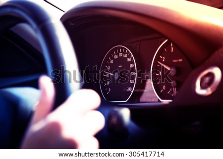 Driving a car at sunset - focus on speedometer