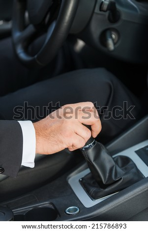 Driving a car. Close-up of man in formalwear driving car
