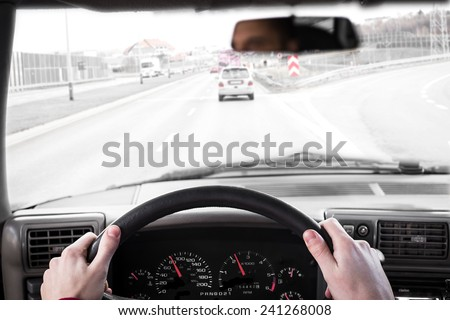 Driving a car. Hand on steering wheel of a car driving on a road. Focus on clocks. - stock photo