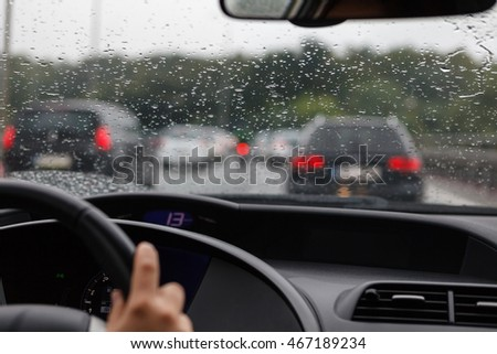 Driving a car in traffic jam in bad weather conditions