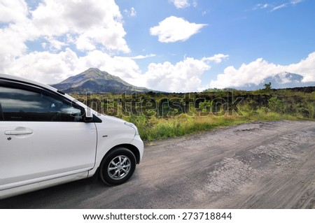 driving across the caldera ridge road among view of extinct crater of the volcano Batur in Bali, Indonesia.