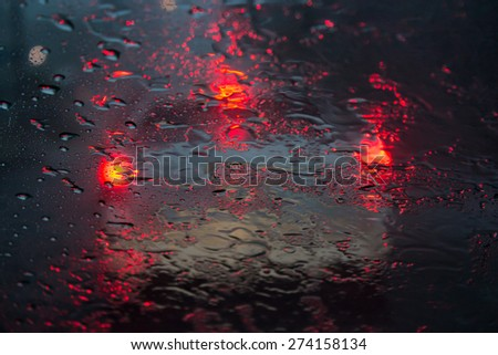 Driving at night in the rain looking at a car in front with their brake lights on distorted by the rain on the windshield. - stock photo