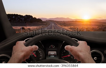 Driving at sunset. View from the driver angle while hands on the wheel. - stock photo