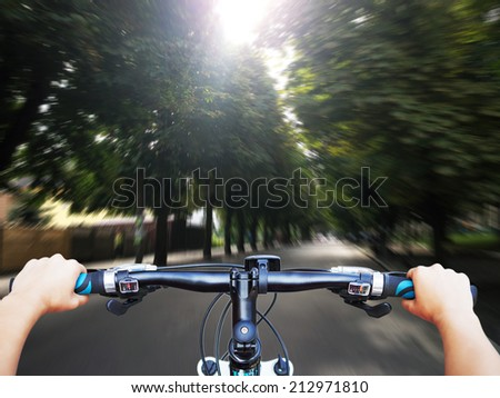 driving bicycle on an asphalt road and meadow sideways - stock photo