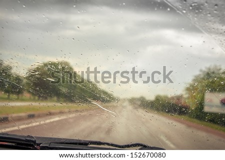 Driving car in the rain on wet road. Rainy weather through the car window. Rain through wind-screen of moving car. View  through the car window in the rain. Car windshield wipers on in the rain. - stock photo
