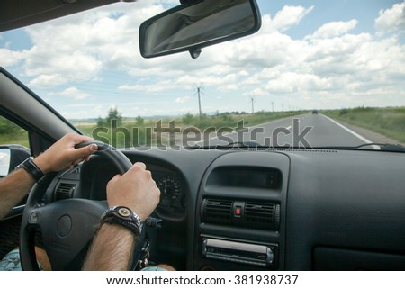 Driving concept  driver hands on wheel and car on road